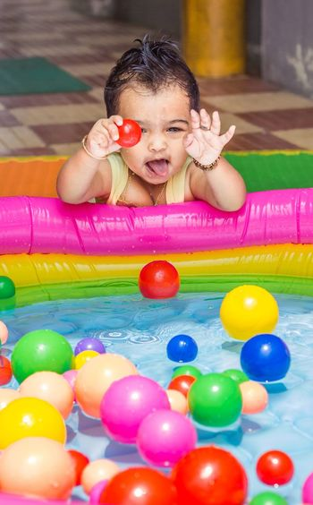 Portrait of smiling girl with colorful balls in wading pool