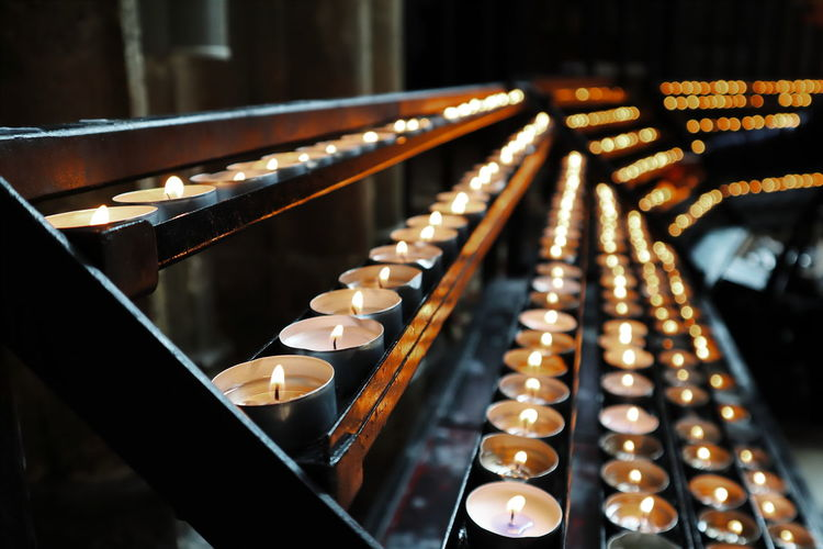 Lit tea light candles on shelves in church