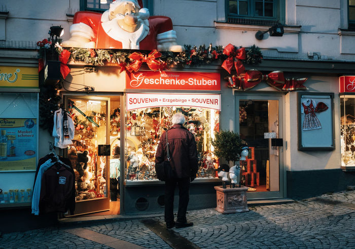 Munich, Bavaria, Germany. Lonely senior man looks at decorated shop window with gifts on Christmas eve at night. Real People Building Exterior Communication Store Rear View Architecture Built Structure Western Script People Retail  Shopping Lifestyles Illuminated Outdoors Christmas Christmas Decoration Christmas Lights Night Lights
