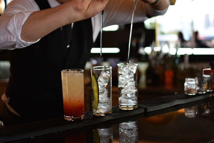 Midsection Of Man Pouring Liquid In Drink At Restaurant