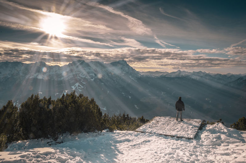 Man Standing At Observation Point Against Snowcapped Mountains