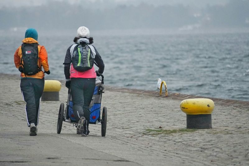 Rear View Of People Walking With Baby Carriage On Pier