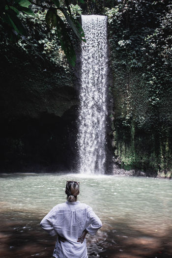 Rear view of woman looking at waterfall in forest