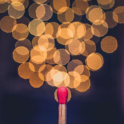 Close-up of matchstick against illuminated defocused lights at night