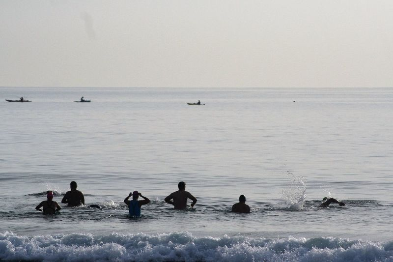 Silhouette Swimmers Enjoying In Sea Against Clear Sky