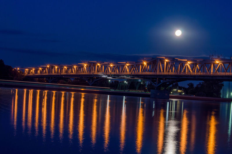 Illuminated bridge over danube river at night