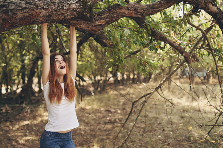 Full length of young woman standing by tree