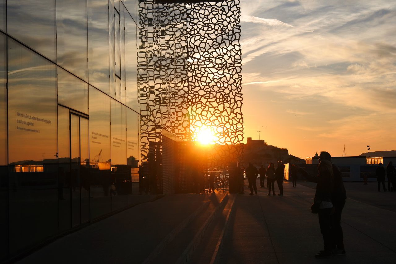 sunset, sky, sun, architecture, built structure, transportation, cloud - sky, silhouette, travel, large group of people, real people, city, sunlight, travel destinations, men, outdoors, building exterior, nature, modern, day, people