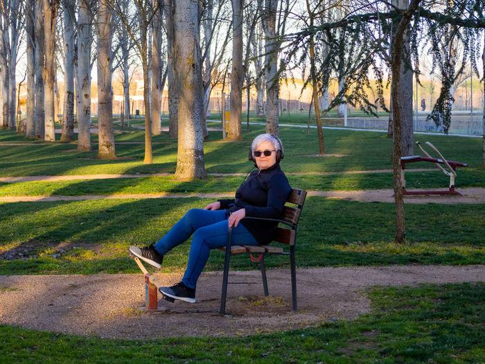 Full length portrait of man sitting on bench in park