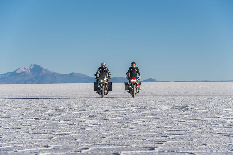 People riding motorcycle on desert against clear sky