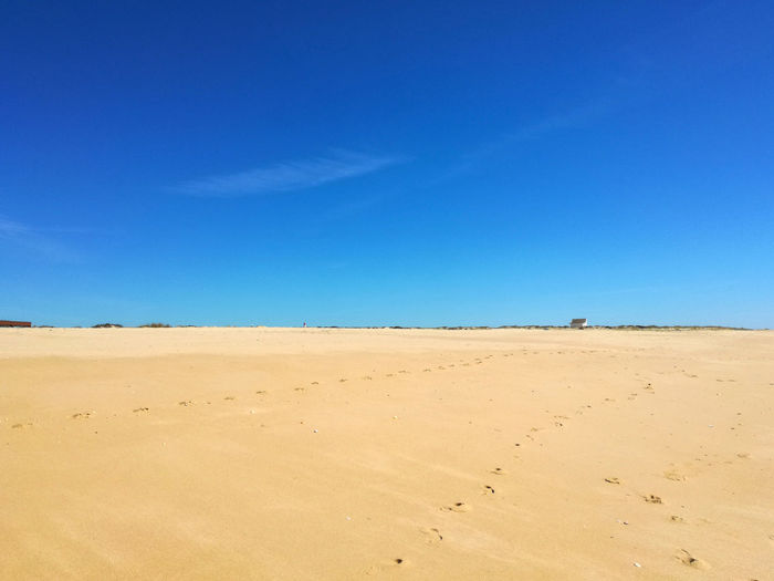 Low Angle View Of Sand Against Clear Blue Sky