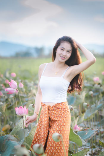 One Person Young Women Young Adult Smiling Leisure Activity Three Quarter Length Women Standing Front View Beautiful Woman Hair Looking At Camera Lifestyles Adult Hairstyle Plant Beauty Casual Clothing Happiness Outdoors