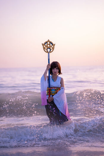 Portrait of young woman wearing costume holding wand at beach during sunset