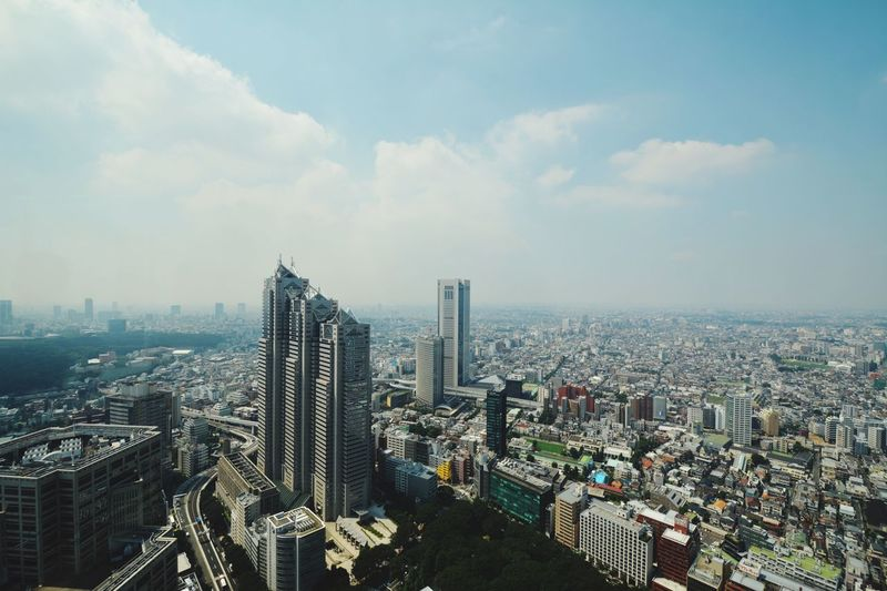 Tokyo metropolitan government building and cityscape against cloudy sky