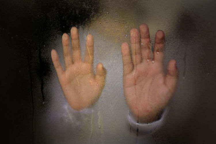 Close-up of hand on wet glass in bathroom