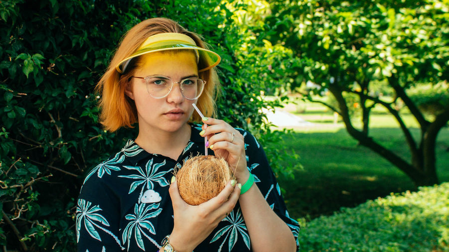 Portrait of young woman drinking coconut water with straw