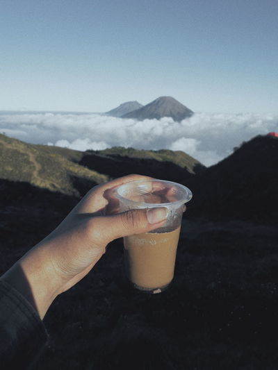 Midsection of person holding coffe  against mountain range