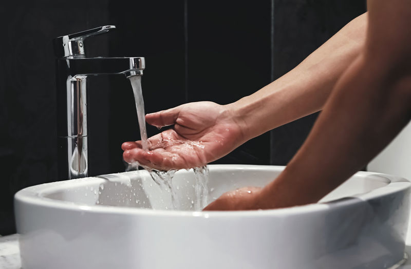 Cropped image of woman washing hands in home