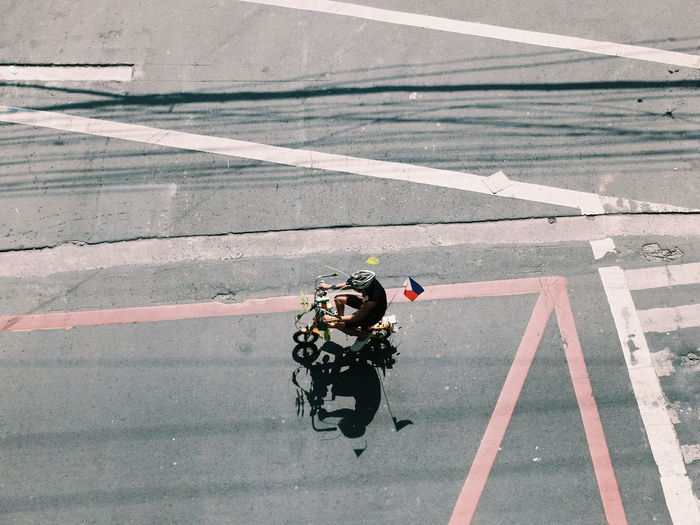 High Angle View Of Man With Philippines Flag Riding Bicycle On Road