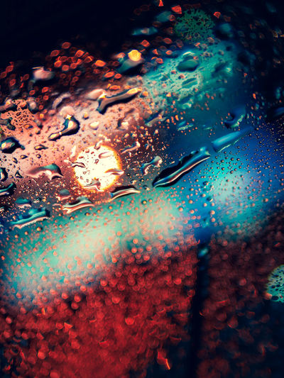 Close-up of raindrops on car windshield