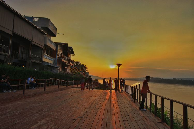 People on pier amidst buildings against sky during sunset