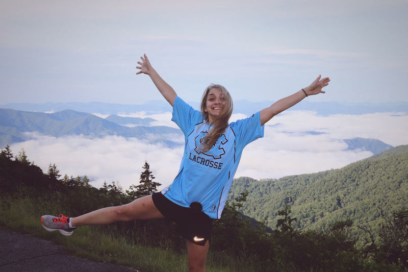 Low angle view of woman with arms raised against sky