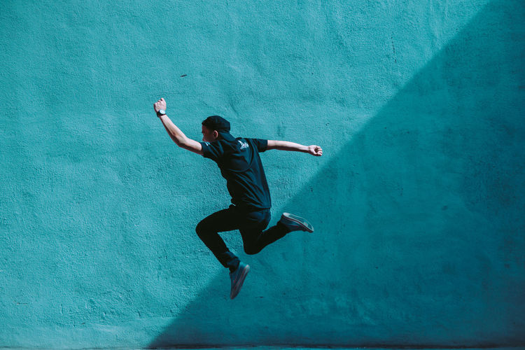 Man jumping against blue wall