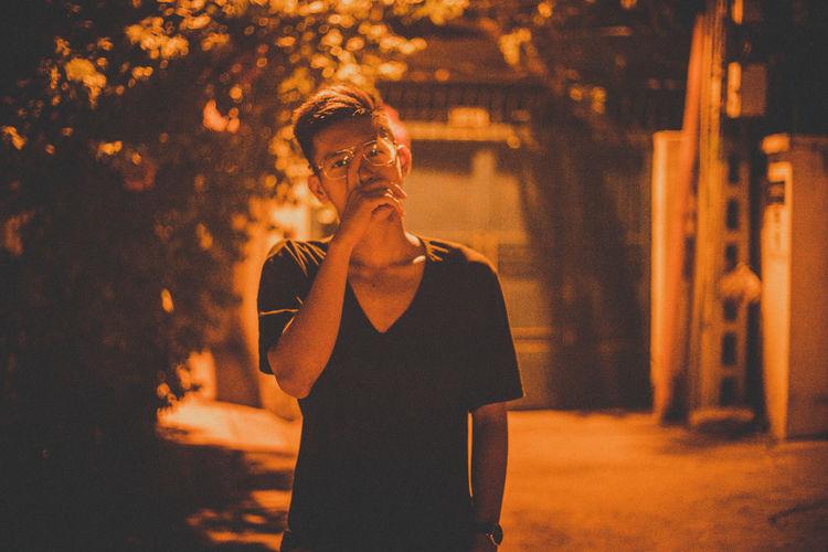 Portrait of teenage boy smoking cigarette at night