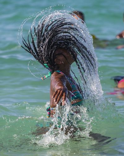 Side view of woman tossing wet hair in sea