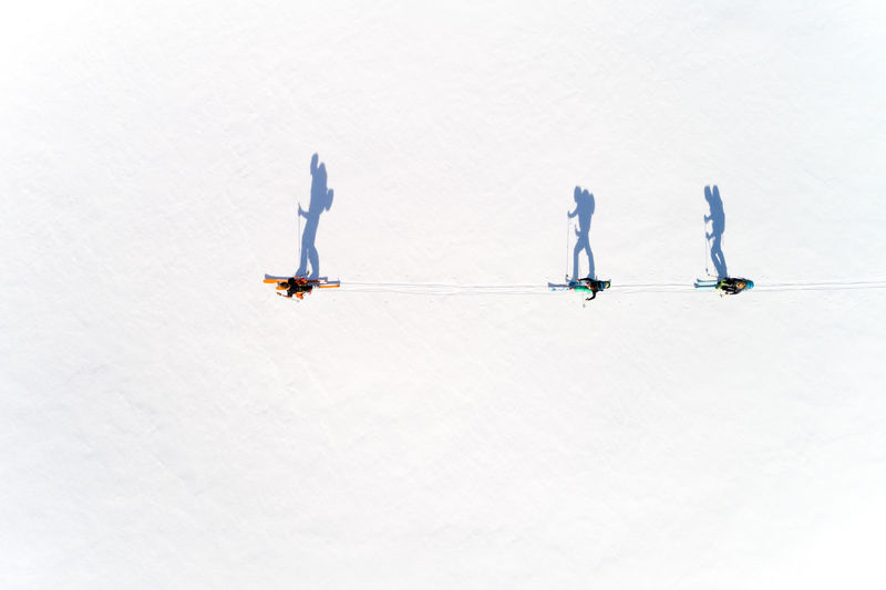 Directly above view of people skiing on snow during sunny day