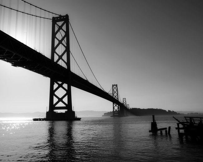 Silhouette of suspension bridge over sea