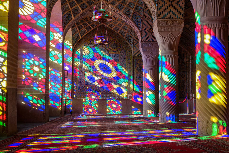 Interior of ornamental Nasir Al-Molk Mosque with colorful stained glass windows at sunrise. It is also known as Pink Mosque. Nasir Al-Mulk Mosque Pink Architecture Architecture And Art Creativity Floral Pattern Molk Mosque Multi Colored Muslim Religion