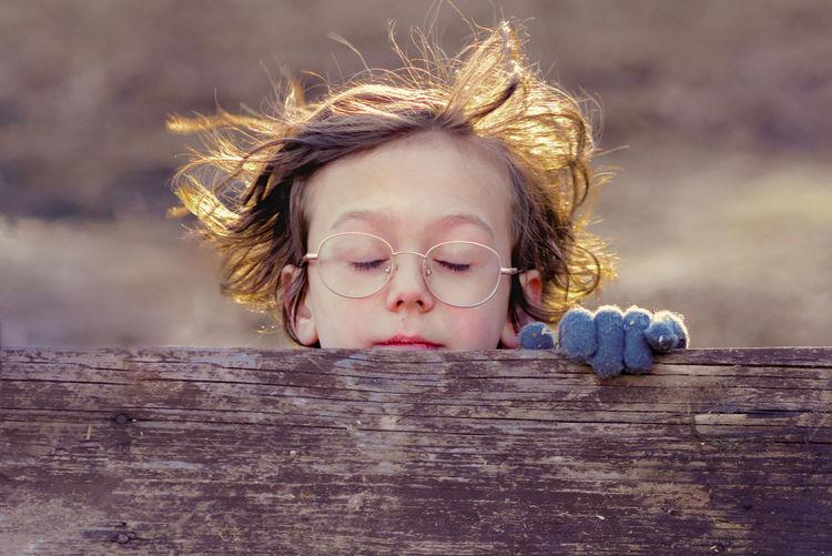 Close-up of cute boy wearing eyeglasses on wood