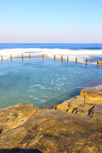 Slow down capture of the Mahon Rock Pool, with smooth waves and water. The railing leading in the pool is visible. Swimming Beach Beauty In Nature Clear Sky Day Horizon Over Water Mahon Pool Nature No People Outdoors Pool Rock Pools Scenics Sea Sky Swimming Pool Tranquility Travel Destinations Water