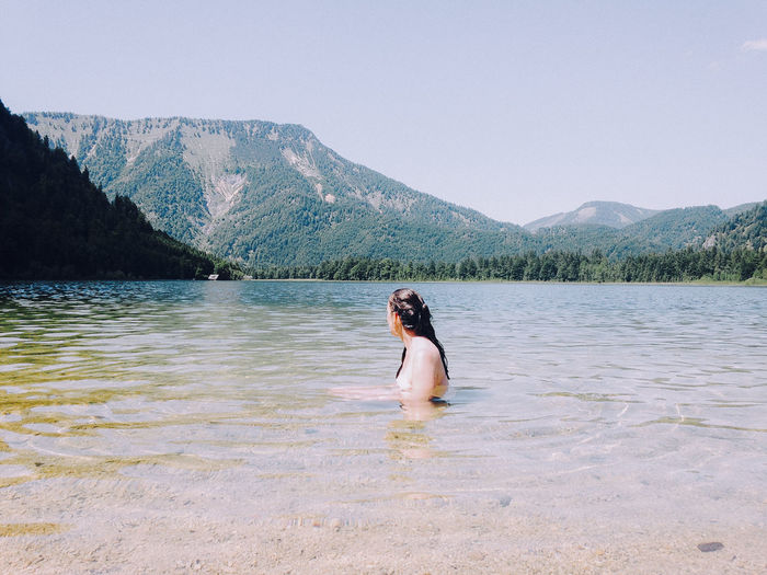 Young woman sitting on lake against clear sky