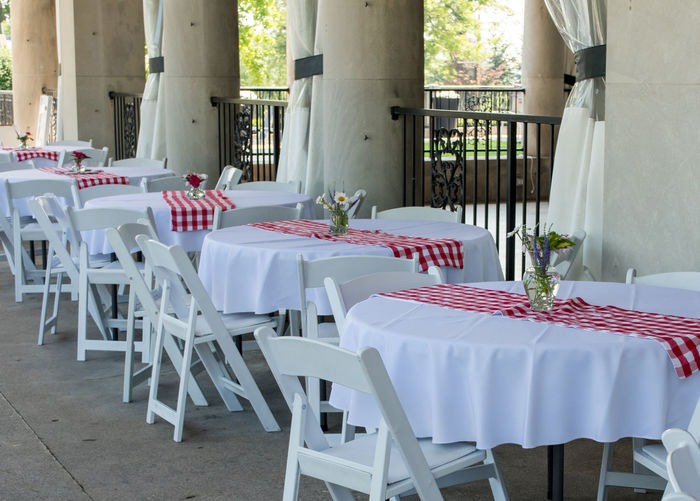 tables with white linens and red checkered runners, are ready for china and silver for a beautiful event Seat Chair Table Place Setting Tablecloth Furniture Setting Absence Arrangement White Color Flower Restaurant No People Empty Dining Table Flowering Plant Indoors  Nature Wedding Event Glass Flower Arrangement Getting Ready Event Hall Wedding Venue
