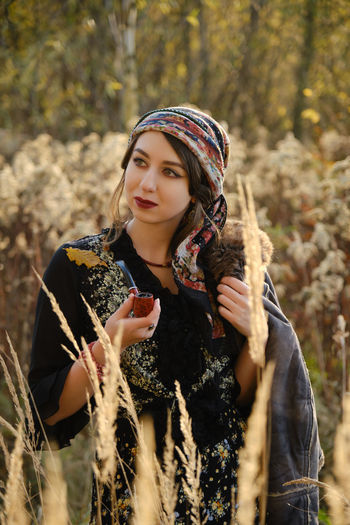Young gypsy woman smoking pipe in autumn dry grass, looking aside