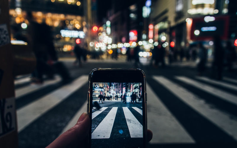 Close-up of person photographing in city at night