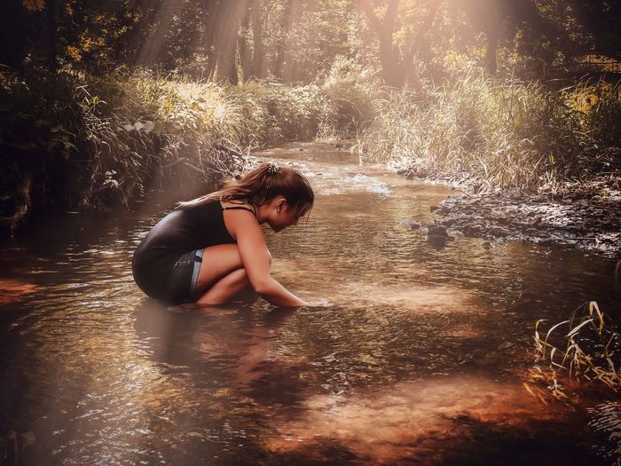 Side view of girl crouching in stream