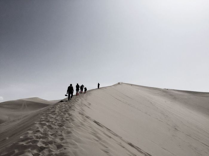 Rear view of people walking on sand dune at desert against clear sky