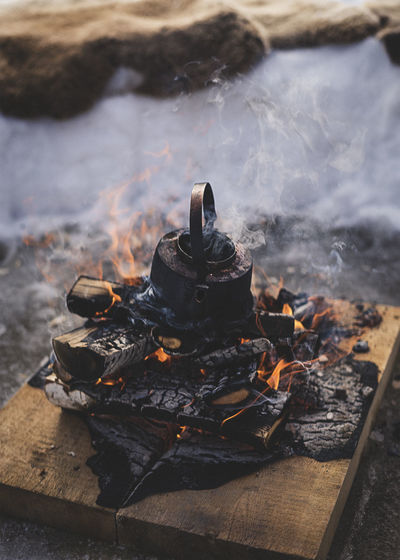 High angle view of tea pot on burning firewood at campsite