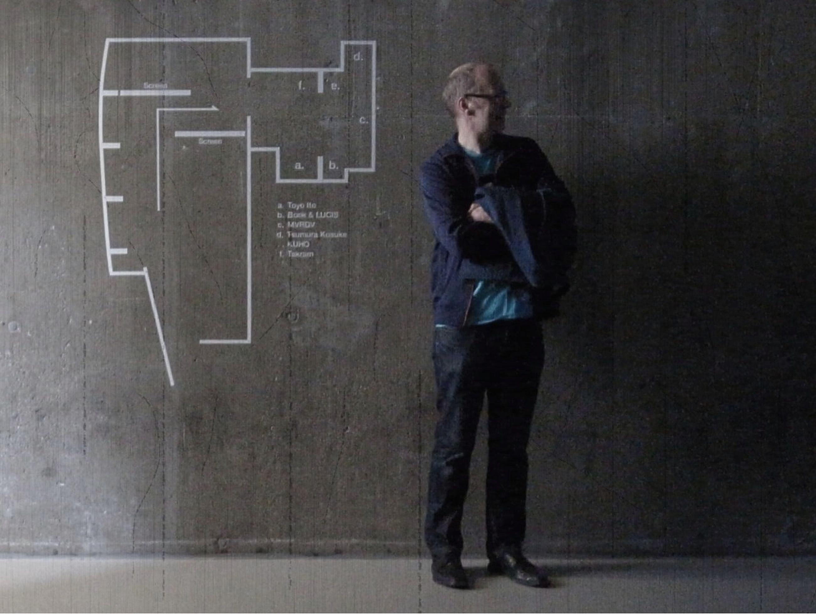 young adult, casual clothing, front view, person, standing, looking at camera, lifestyles, portrait, young men, wall - building feature, full length, three quarter length, architecture, built structure, leisure activity, indoors, hands in pockets