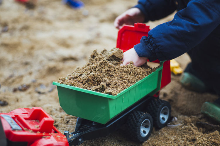 Cropped Image Of Kid Playing With Toy Truck On Sand At Beach