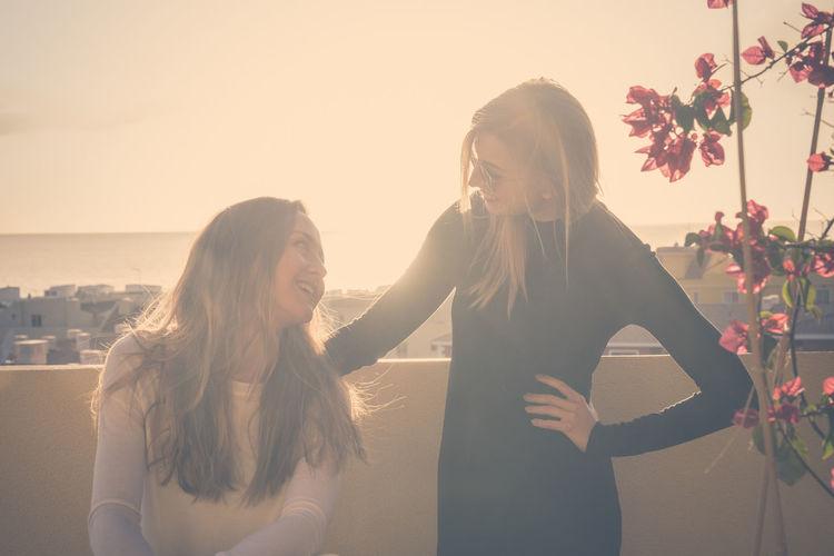 Happy Female Friends On Terrace Against Sky
