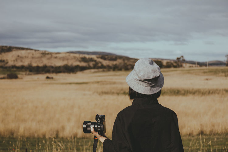 Rear view of woman wearing hat standing with camera on field against sky