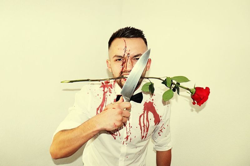 Portrait Of Young Man With Blood On Face And Uniform Holding Rose And Knife Against White Wall