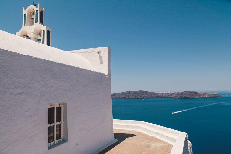 Chapel at santorini island by sea against clear blue sky
