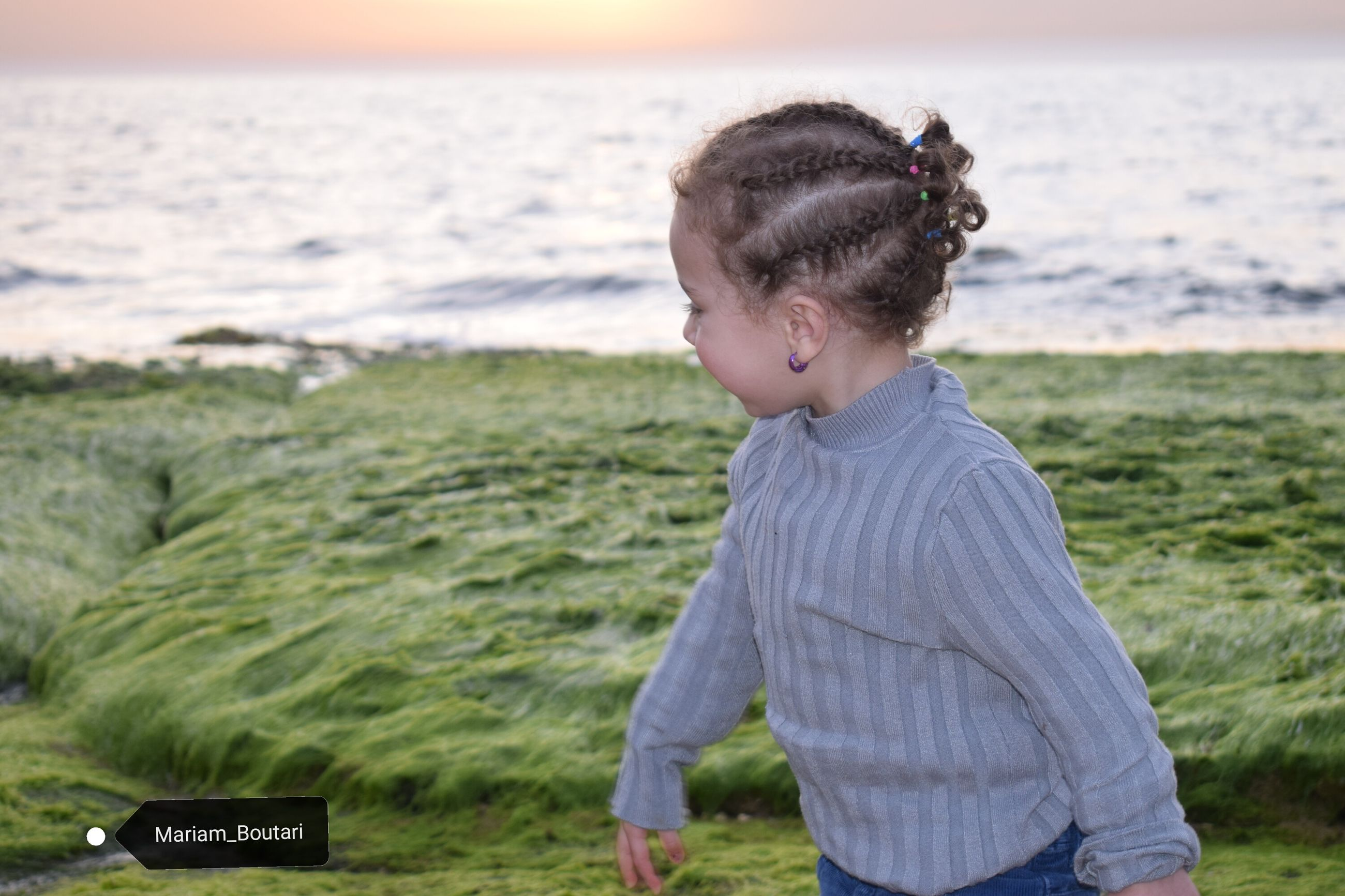 water, sea, land, child, one person, childhood, casual clothing, real people, beach, leisure activity, side view, nature, focus on foreground, day, lifestyles, standing, horizon over water, outdoors, hairstyle, innocence