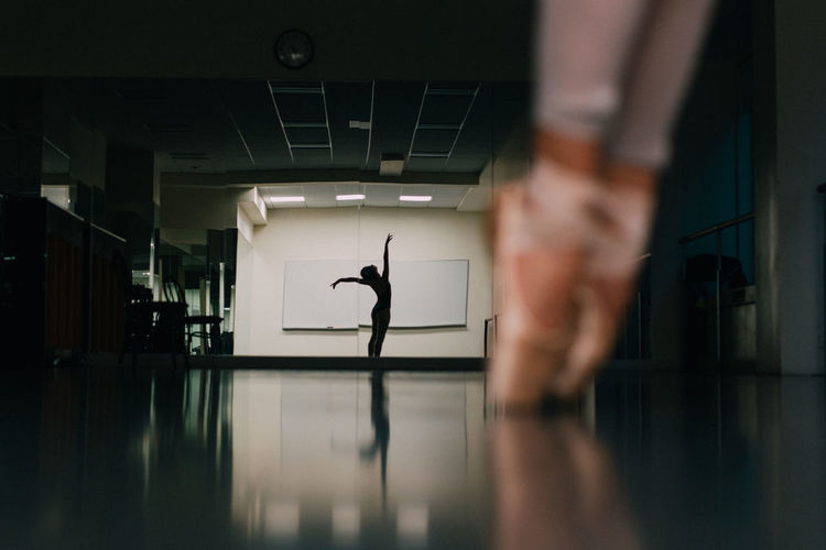 Low Section Of Woman Practicing Ballet With Reflection In Mirror At Dance Studio