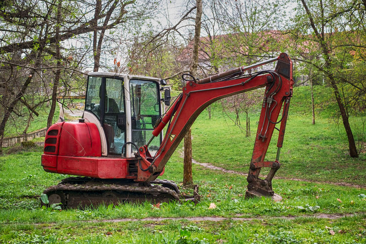 a small red excavator in the woods A Small Red Excavator In The Woods Land Plant Tree Day Nature Field Grass No People Abandoned Land Vehicle Red Mode Of Transportation Outdoors Green Color Forest Machinery Growth Old Bare Tree Absence